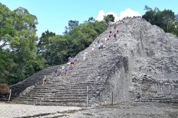 Tall stone pyramid surrounded by trees with people climbing to the top at Coba ruins, Mexico.