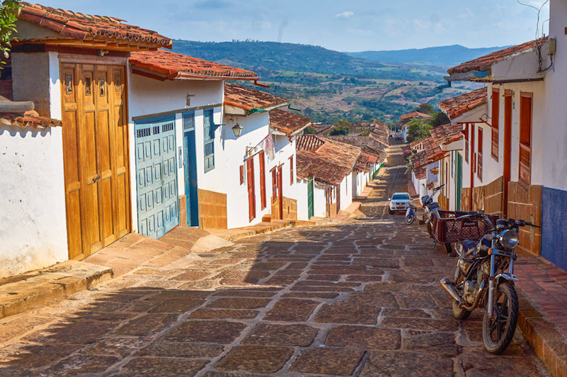 Cobblestoned street sloping downhill between colourful red-tiled houses and a view of countryside beyond in Barichara, Colombia.