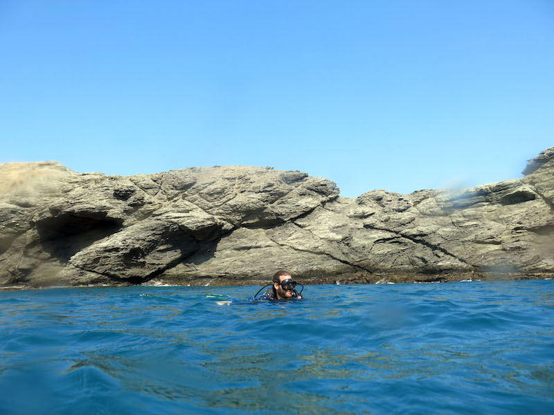Man floating in the blue water with scuba gear on with rocks behind in Taganga, Colombia.