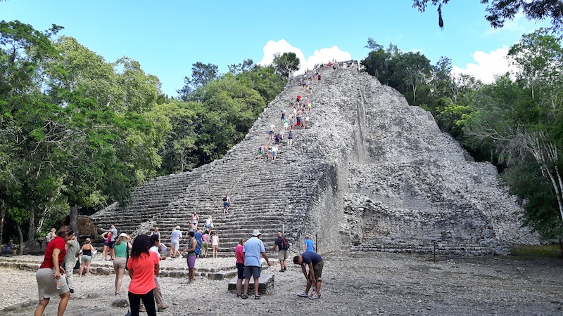 Lots of people around the base of the pyramid while others climb to the top at Coba mayan ruins, Mexico.