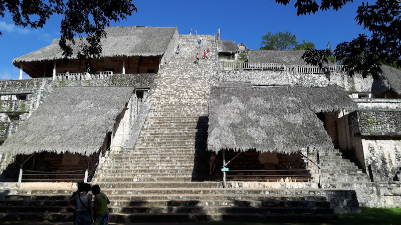 The tall stone stairway with palapa roofs sheltering sculptures up the Acropolis at Ek' Balam, Mexico.