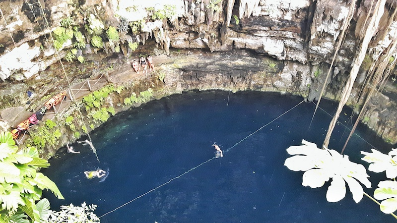 Looking down at deep blue water in Cenote Oxman from high above in Valladolid, Mexico.