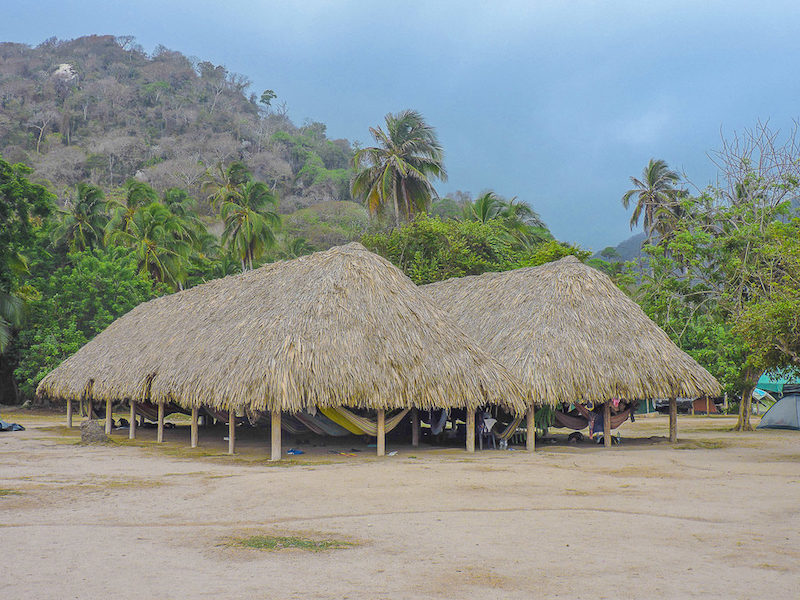 Rows of hammocks under a palapa roof on the beach backed by palm trees in Tayrona National Park, Colombia.