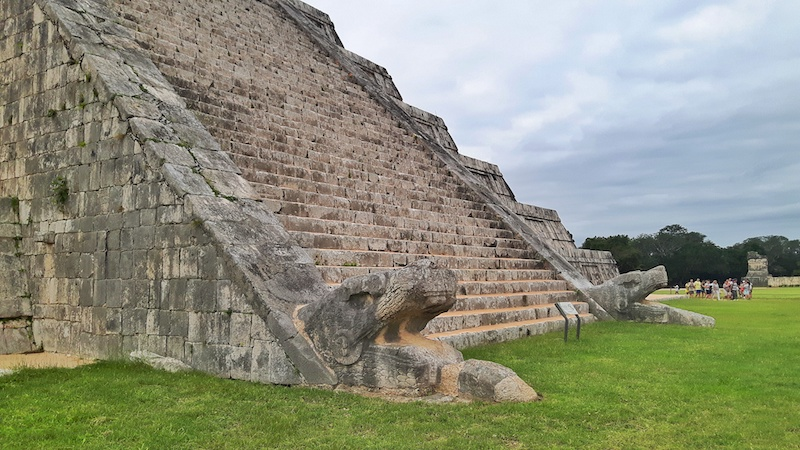 Serpents head at base of pyramid in Chichen Itza Mexico.