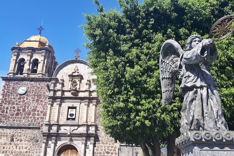 The stone church tower and angel statue in the main plaza of the pueblo magico, Tequila, Mexico.