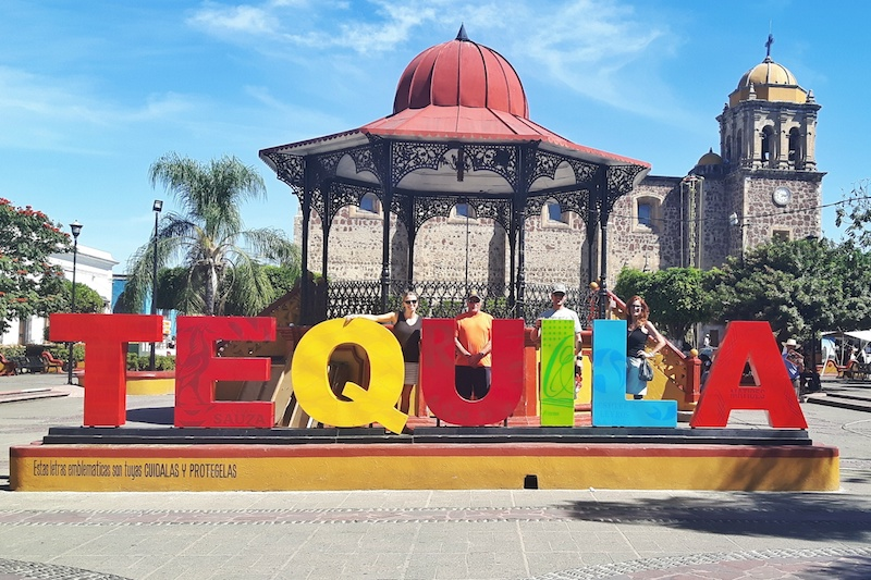 People standing behind the colourful 'Tequila' sign in Jalisco, Mexico.