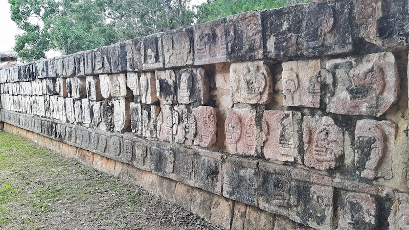 Ancient stone wall with a carving of a skull on each stone at Chichen Itza, Mexico