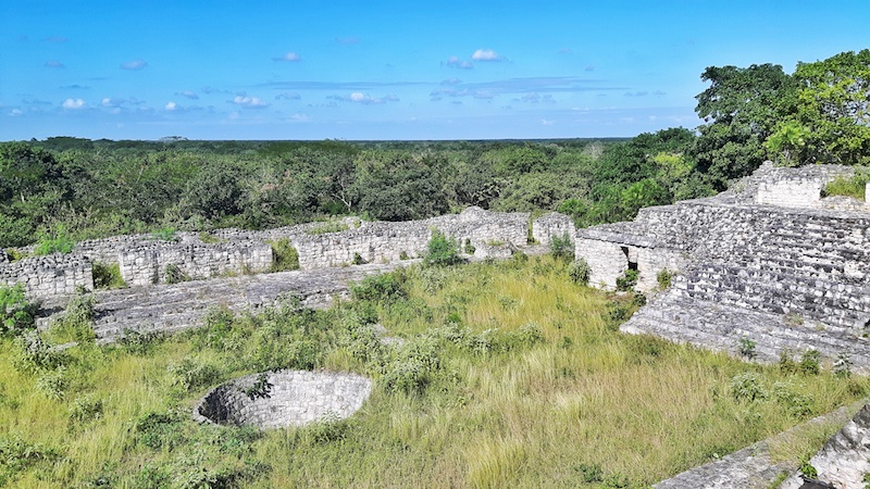 An ancient plaza filled with long grass and a stone well on the Acropolis at Ek Balam ruins, Mexico.