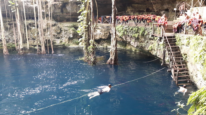 Swimming to the stairs in Cenote San Lorenzo Oxman with a rope for help in Mexico.