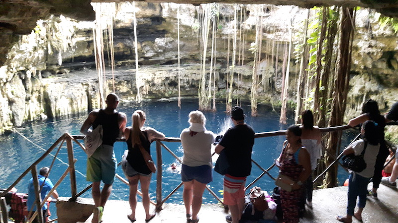 People looking down at Cenote Oxman, Valladolid Mexico.