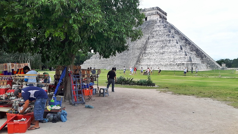 Vendors under a tree in front of the Kukulkan pyramid in Chichen Itza, Mexico