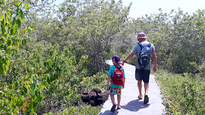 Man and boy hiking a path to Punta Carola with backpacks in San Cristobal, Galapagos.