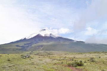 Snow-capped Cotopaxi volcano with steam rising from top in Ecuador.