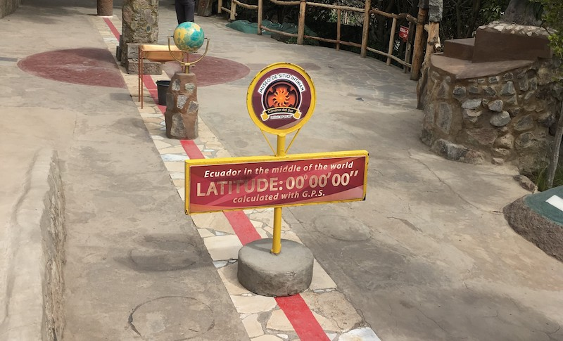 Red painted line and a sign to show the equator line in Ecuador.