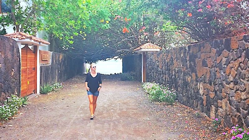 Woman in shorts walking down a colourful alley in Santa Cruz, Galapagos Islands.
