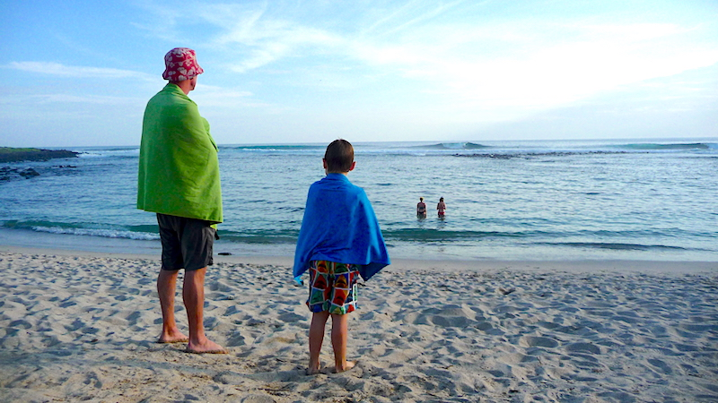Man and boy on a beach wrapped in travel towels looking out to sea in San Cristobal, Galapagos.