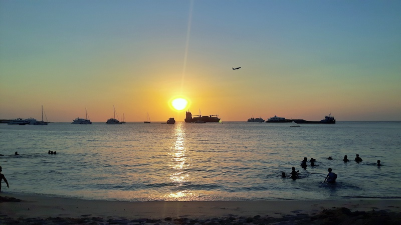 sunset on Galapagos beach with boats and a plane taking off, Ecuador.