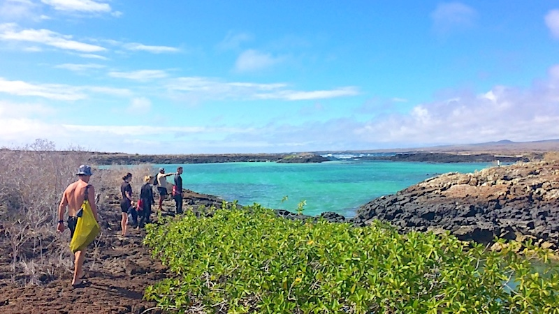 People walking to a blue lagoon to snorkel on the 360 day tour in San Cristobal, Galapagos.