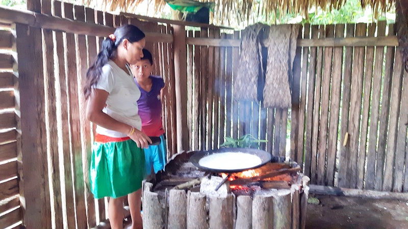 Indigenous woman standing over open fire making bread in Cuyabeno Reserve, Ecuador Amazon.