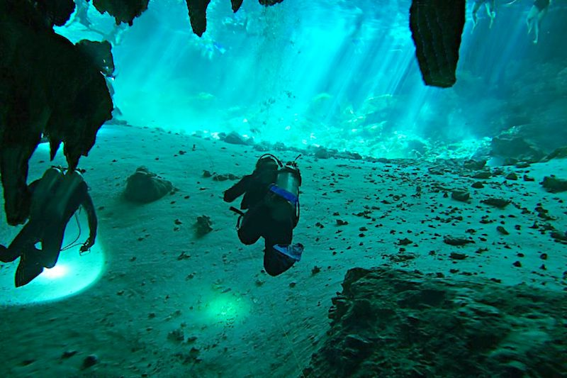 Divers in clear blue water in Cenote Dos Ojos, Mexico.
