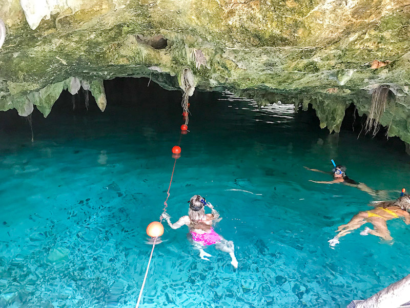 People swimming inside the clear blue water of Gran Cenote, Mexico.