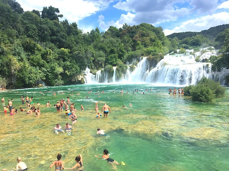 People swimming at the waterfall in Krka National Park, Croatia.