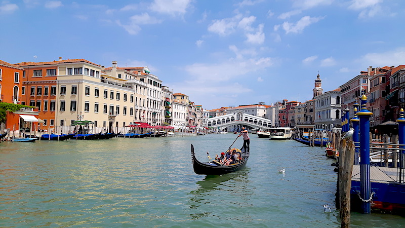 Gondola on Grand Canal with Rialto Bridge behind, Venice Italy.