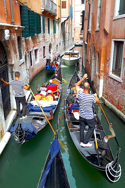 Line of gondolas on narrow Venice canal, Italy.